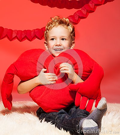 Little blond boy with heart pillow