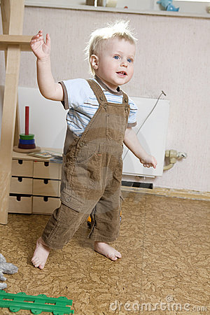 Little blond boy walking around room