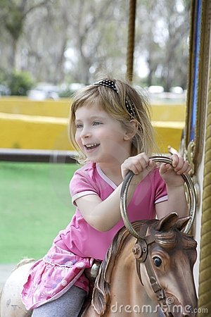 Little blond girl playing horses merry go round