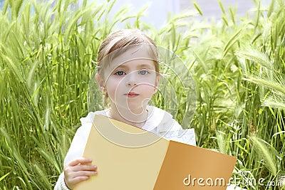 Little blond girl reading book green spikes garden