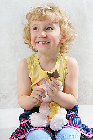 Free Little Blonde Curly Girl Eating Chocolate With Toy Stock Photos - 1837153