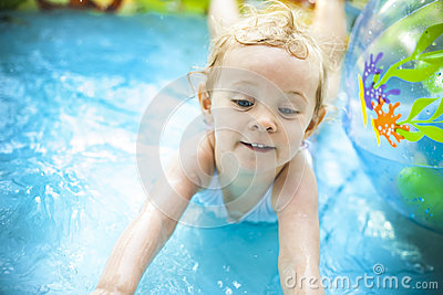 Little blondie girl in swimming pool