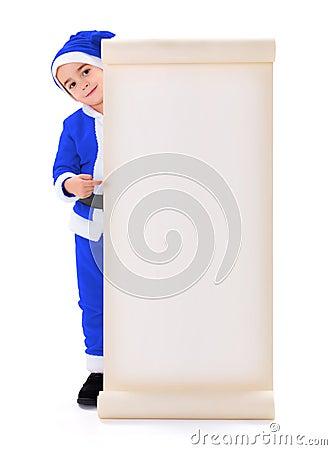 Little blue Santa Claus boy pointing at big wish list