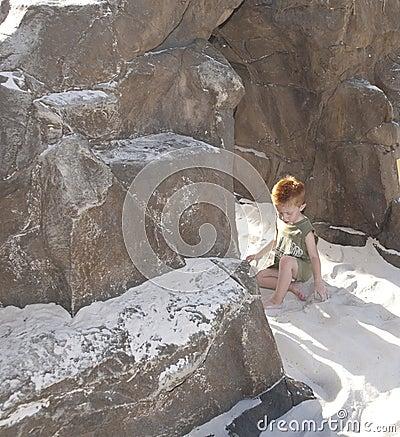 Little boy on beach near rocks alone