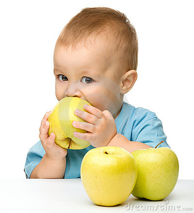 Little boy biting yellow apple