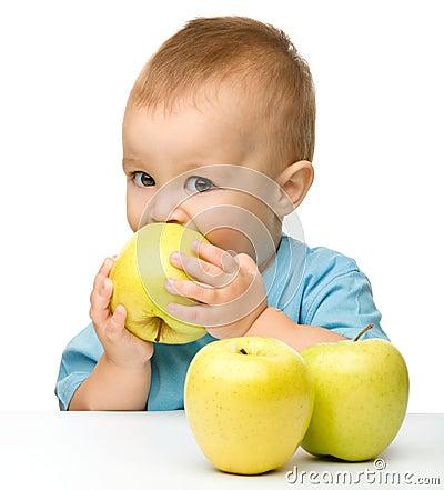 Little boy biting yellow apple