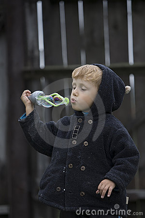 Little boy blows soap bubbles