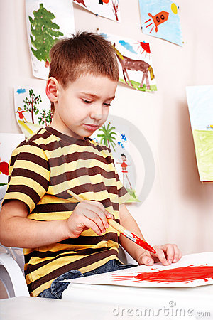 Little boy  with brush draw red sun in play room.