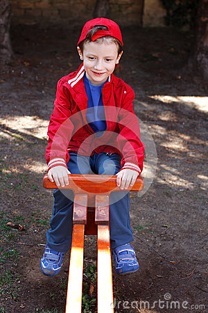 Little boy in cap sitting on seesaw