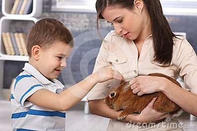Little boy caressing pet rabbit handheld by mum