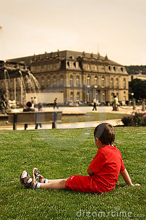 Little boy in the city center on the grass