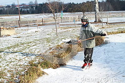 Little boy cleaning ice on pond