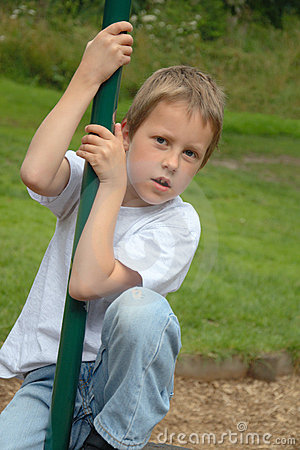 Little boy climbing pole on playground