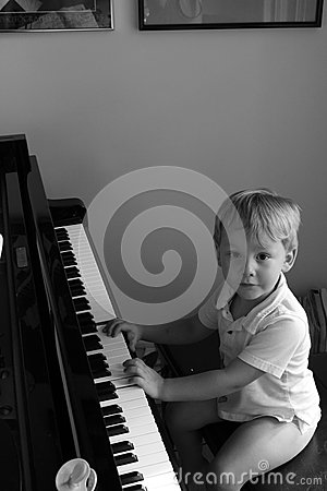 Little boy at concert grand piano