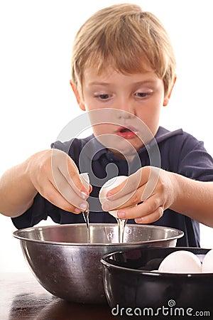 Little boy cracking an egg