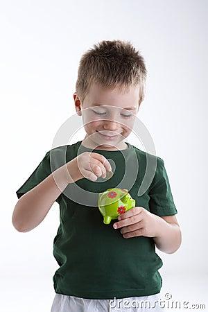 Little boy depositing money in his piggy bank.
