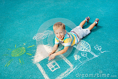 Little boy drawing chalk image on the ground