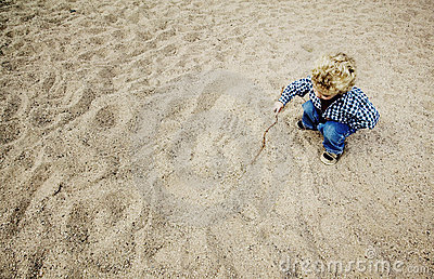 Little Boy Drawing in the Sand
