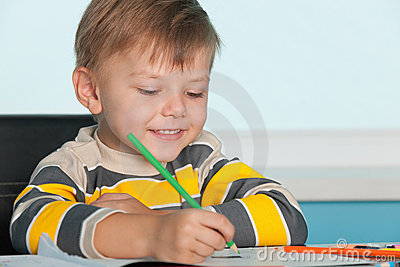 Little boy draws at the desk