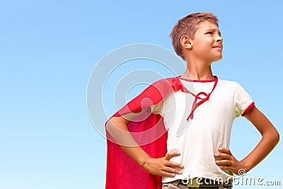 Little boy dressed up as a superhero looking away