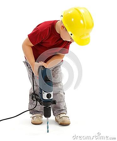 Little boy drilling in ground