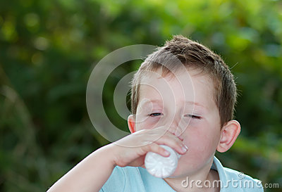 Little boy drinking milk from a small white bottle