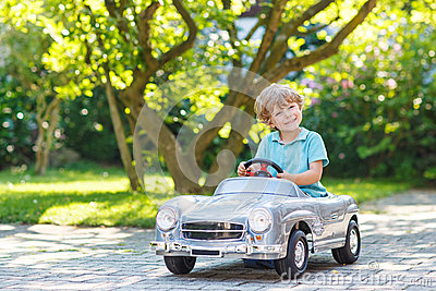 Little boy driving big toy old car, outdoors