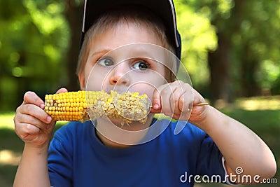 Little boy eating corn on the cob