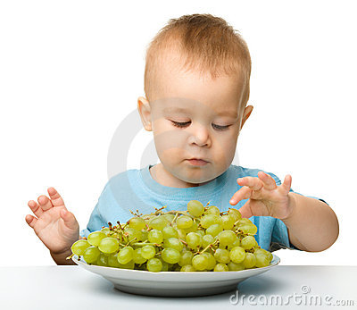 Little boy is eating grapes