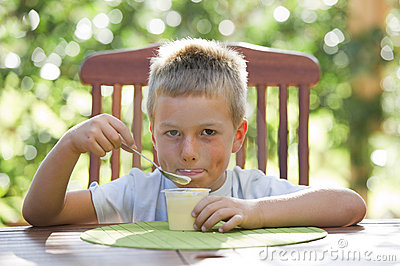 Little boy eating pudding
