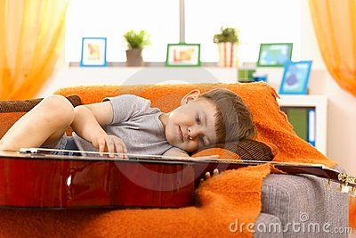 Little boy examining guitar on sofa