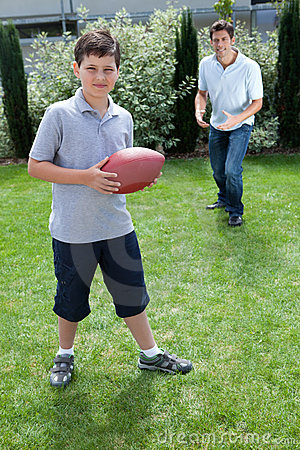 Little boy and father playing american football