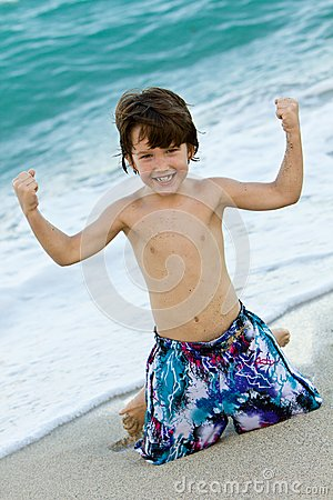 Little boy flexing muscles on beach