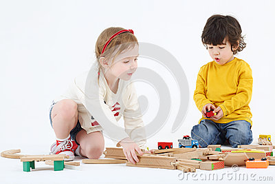 Little boy and girl build railway from wooden parts