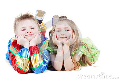 Little boy and girl in carnival suits lie on floor