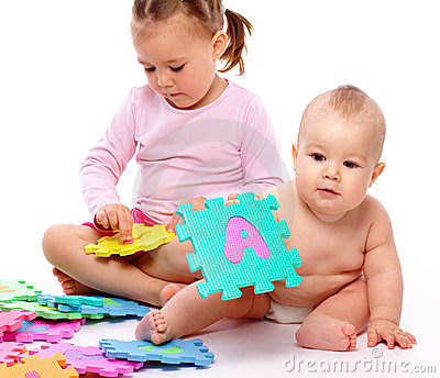 Little boy and girl are playing with alphabet
