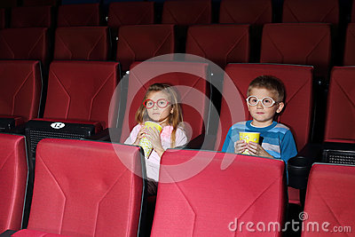 Little boy and girl with popcorn watching a movie