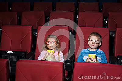 Little boy and girl with round glasses eating popcorn