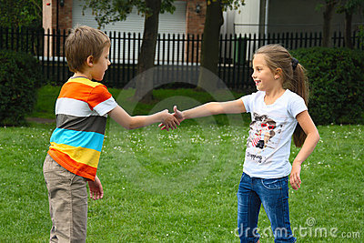 Little boy and girl shaking hands in park, outdoor
