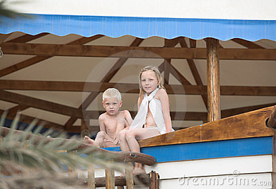 Little boy and girl sit on a wooden counter