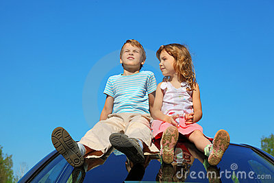 Little boy and girl sitting on car roof