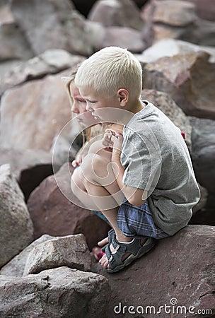 Little boy and girl squat on sharp rocks