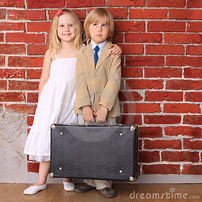 Little boy and girl standing with a suitcase