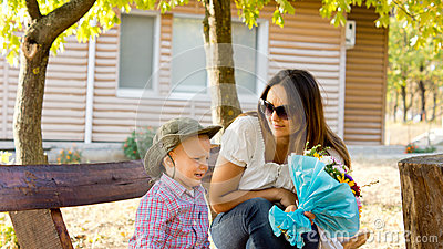 Little boy giving Mum a bouquet of flowers