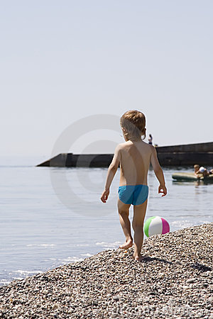 Little boy goes on stony seacoast