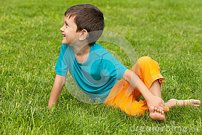 Little boy on the grass looking aside
