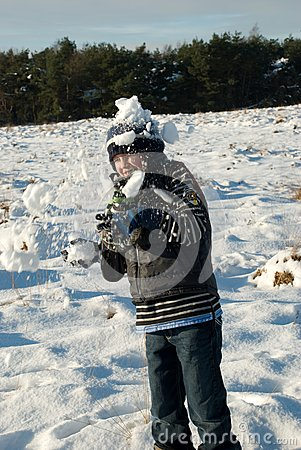 Little boy having fun in snow with snowballs
