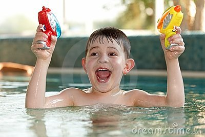Little boy having fun with water pistols