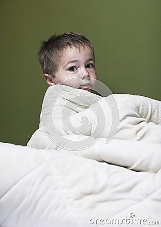 Little boy hides under white blanket