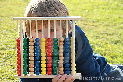 Little boy hiding behind an abacus